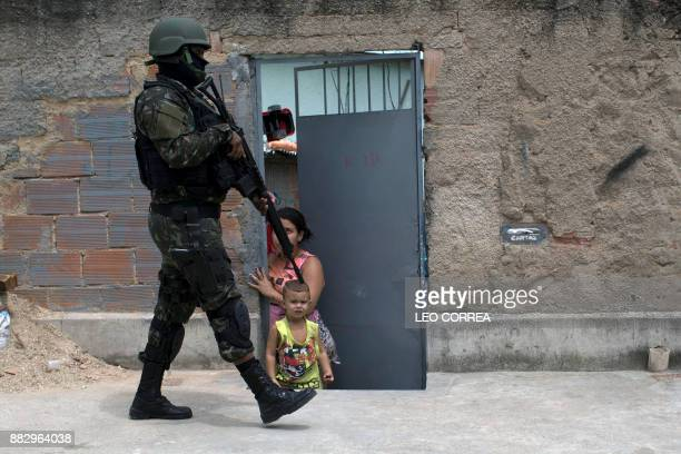 Brazilian army soldier walks past a child during a security operation at Barbante favela where earlier in the week alleged drug traffickers destroyed...