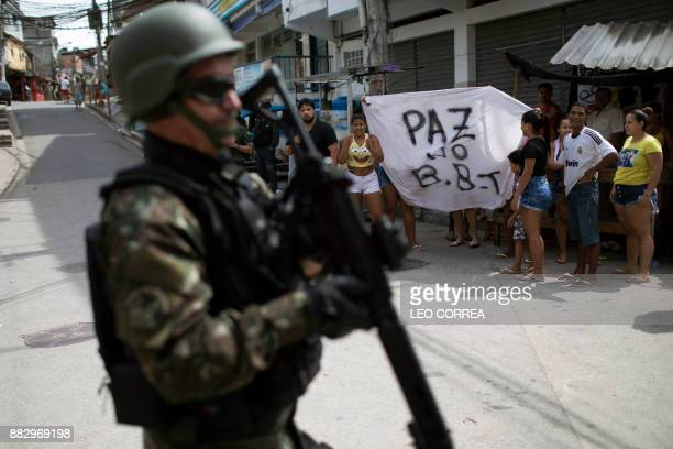 A Brazilian army soldier walks past a group of residents holding a sign demanding peace during a security operation at Barbante favela in Rio de...