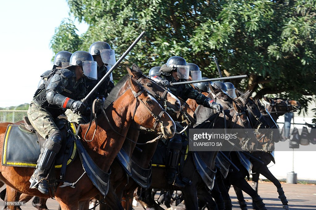 Brazilian Army soldiers mounted and in riot gear conduct a drill at the Fire Department headquarters in Brasilia, on May 3, 2013, as part of the security measures ahead of the Confederation Cup whi...