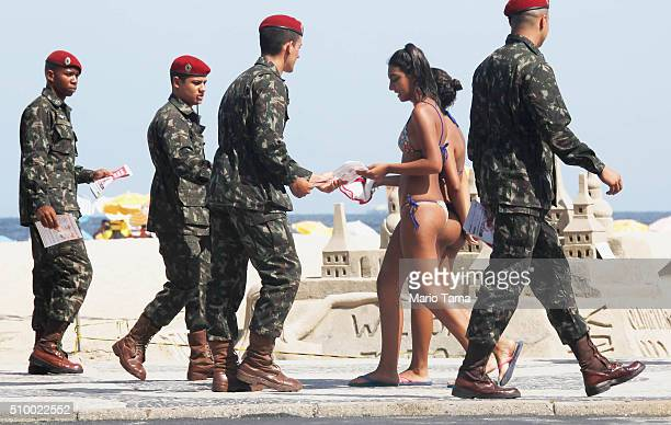 Brazilian Army soldiers pass out pamphlets on Copacabana beach warning of the dangers of the Zika virus and how to protect against mosquitos on...