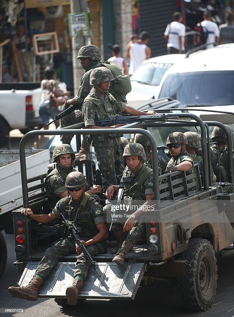 Brazilian Army soldiers patrol in the occupied Complexo da Mare, one of the city's largest favela complexes, on May 9, 2014 in Rio de Janeiro, Brazil. The Brazilian government has deployed nearly 3,000 federal troops to occupy the group of violence-plagued slums ahead of the June 12 start of the 2014 FIFA World Cup. The group of 16 communities house around 130,000 residents and had been dominated by drug gangs and militias. Mare is located close to Rio's international airport and has been mentioned as a likely pacification target for the police amid the city's efforts to improve security ahead of the 2014 FIFA World Cup and Rio 2016 Olympic Games.