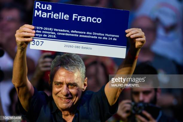 Brazilian artist Chico Buarque holds a sign reading Marielle Franco St during a Fernando Haddad campaign rally in Rio de Janeiro Brazil on October 23...