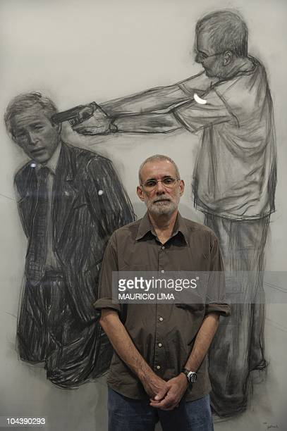 Brazilian artist Gil Vicente poses for a portrait in front of his works depicting former US President George W Bush ahead of the official opening of...