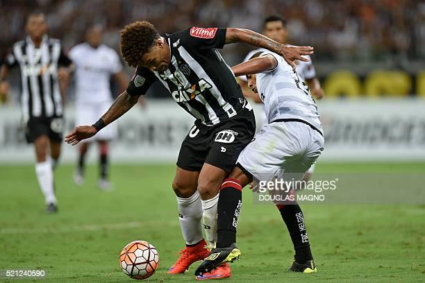 Brazilian Atletico Mineiro player Junior Urso vies for the ball with Peruvian Melgar player Minzun Quina during their 2016 Libertadores Cup match at...