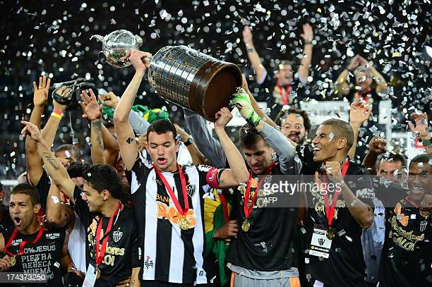 Brazilian Atletico Mineiro's captain Rever holds up the Libertadores Cup after the second leg final football match against Paraguayan Olimpia the...