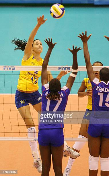 Brazilian attacker Sheilla Castro spikes the ball over Kenyan blockers Enda Rotich and Brackcides Khadambi during a match of the women's World Cup...