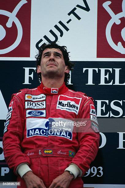 Brazilian Ayrton Senna listening to his national anthem on the podium after winning the Japanese Grand Prix with his McLaren-Ford.