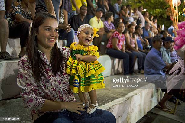 A Brazilian baby girl in a traditional costume looks at a performance during a street festival beside a beach where Ghana's national football team...