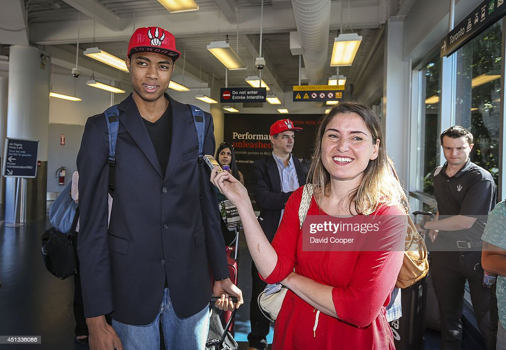 TORONTO, ON- JUNE 27 - Brazilian Basketball player Bruno Caboclo drafted 20th over all by the Raptors arrives on Porter Airlines from Newark NJ at Billy Bishop Airport in Toronto. Toronto Star reporter Isabel Teotonio (in Red) talks to Bruno as he arrived. June 27, 2014.