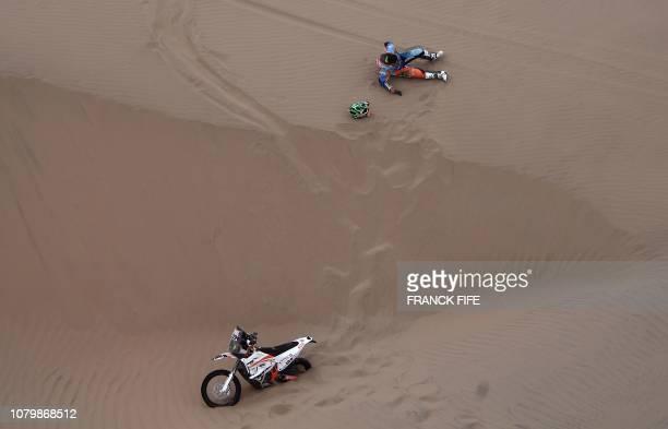 TOPSHOT Brazilian biker Marcos Colvero lies on the sand after crashing during Stage 3 of the Dakar 2019 between San Juan de Marcona and Arequipa Peru...