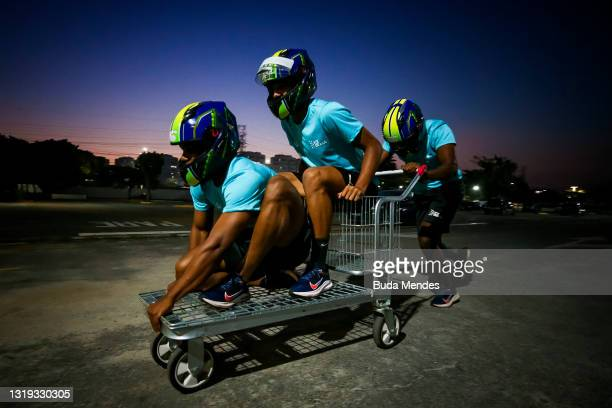 Brazilian bobsledders Rafael Souza, Gustavo Ferreira and Edson Martins play with a trolley in a parking lot of a supermarket on May 20, 2021 in Sao...