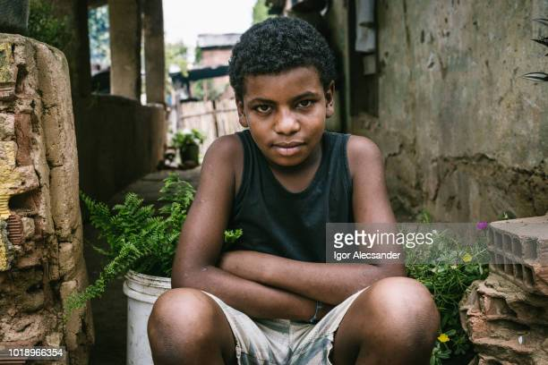 brasilianische junge sitzt auf der veranda des hauses - brasilianischer abstammung stock-fotos und bilder