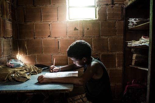 Brazilian boy studying at home 1018966316