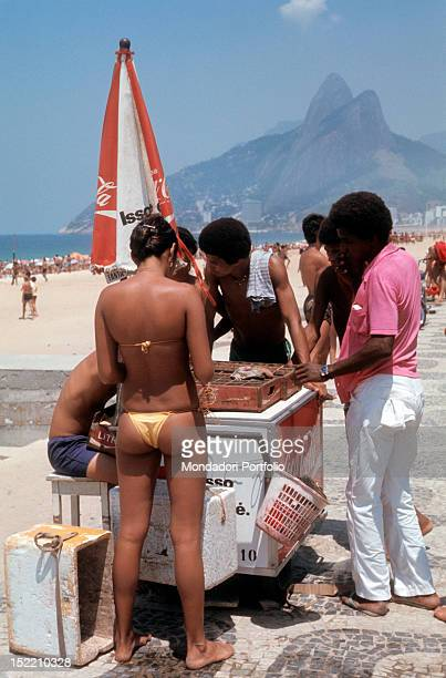 Brazilian boys and a girl wearing bathing costumes waiting for their turn to be served by an hawker on Copacabana beach Rio de Janeiro May 1977