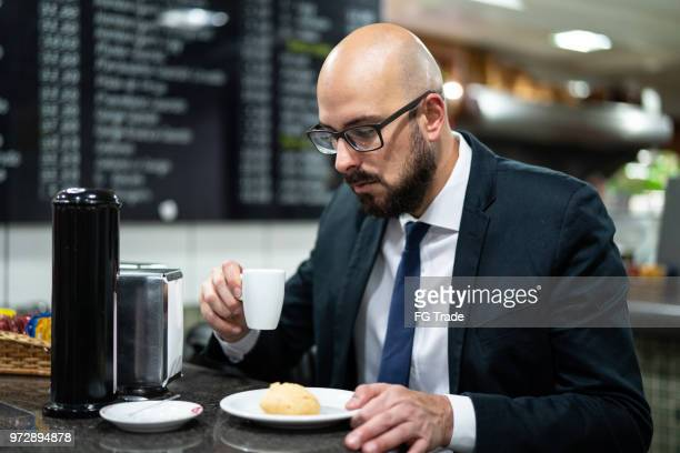 brazilian business man eating pao de queijo - queijo stock pictures, royalty-free photos & images