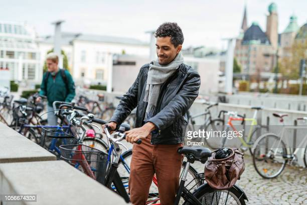 brazilian businessman going to work and leaving bicycle on the parking lot - bicycle parking station stock photos and pictures