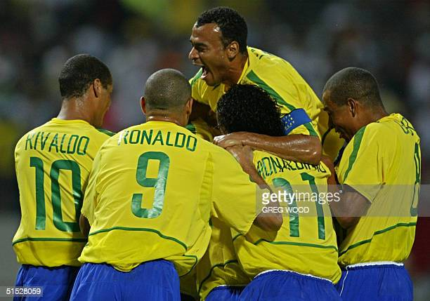 Brazilian captain Cafu jumps over teamates to celebrate Rivaldo's goal 08 June 2002 at the Jeju World Cup Stadium in Seogwipo before the first round...