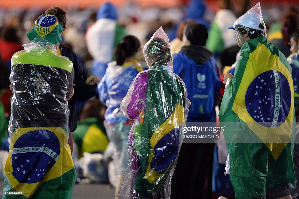 Brazilian Catholic faithfuls wear nylon raincoats during the World Youth Day (WYD) opening mass, at Copacabana beach in Rio de Janeiro, Brazil, on July 23, 2013. The highlight of the landmark visit of Pope Francis to the world's most populous mainly Catholic country will be WYD, a five-day event that kicks off today. Pope Francis's popularity on his Latin American home turf posed a challenge to Brazilian authorities Tuesday after adoring crowds mobbed his car on his arrival on Monday.