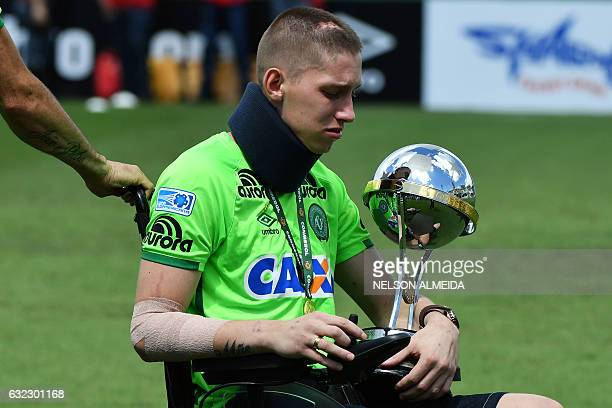 Brazilian Chapecoense goalkeeper Jackson Follmann a survivor of the LaMia airplane crash in Colombia holds the Copa Sudamericana trophy at the Arena...