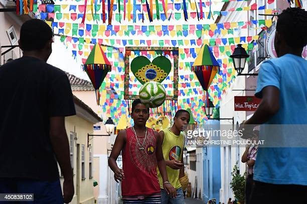 Brazilian children play football on a street in Salvador De Bahia on June 18 2014 during the Group B football match between Spain and Chile in the...