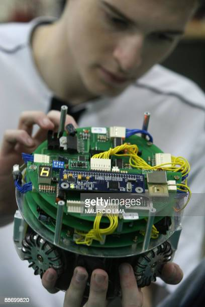 Brazilian computing engineering student Gabriel Francischini makes some adjustments to an inteligent robot invented to play football ahead of the...