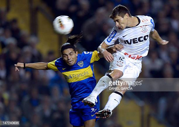 Brazilian Corinthians' midfielder Alex heads the ball in front of Argentinian Boca Juniors' midfielder Walter Erviti during their Copa Libertadores...