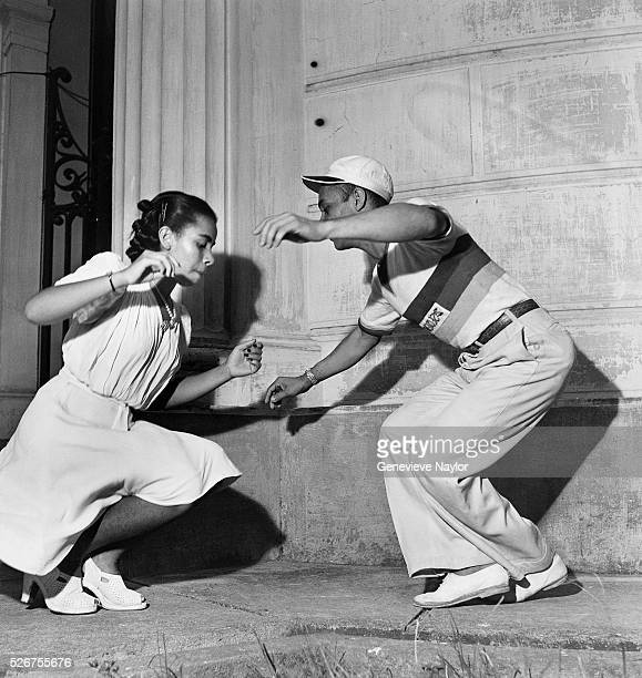 A Brazilian couple dance the samba in front of a building