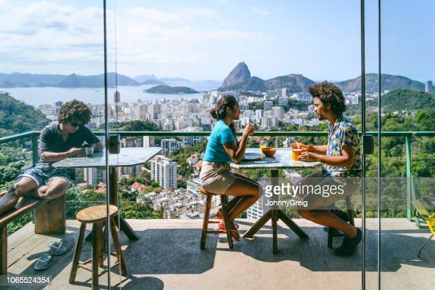 brazilian couple on terrace,  sugar loaf mountain in background - hotel breakfast stock pictures, royalty-free photos & images