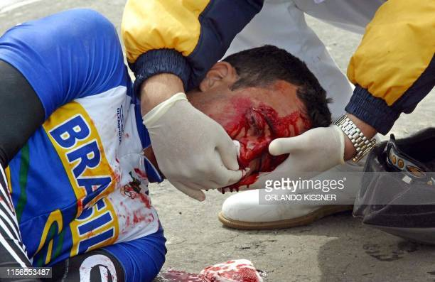Brazilian cyclist Diogo Bonini Marquez recieves medical attention after his accident during the final round in cycling of the VII South American...