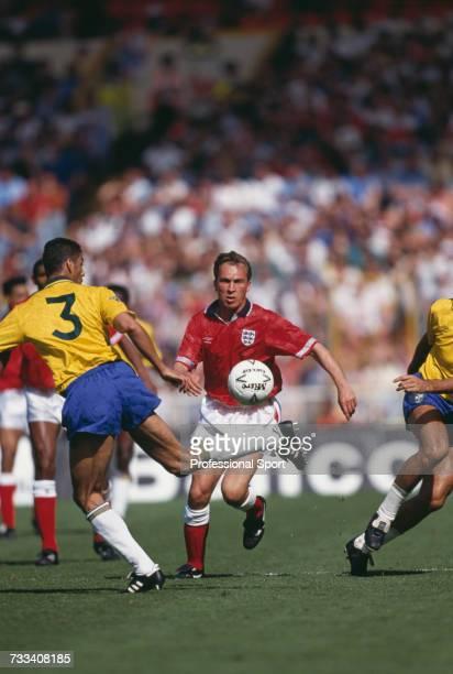 Brazilian defender Carlos Mozer back heels the ball as England midfielder David Platt runs forward to intercept in the international friendly match...
