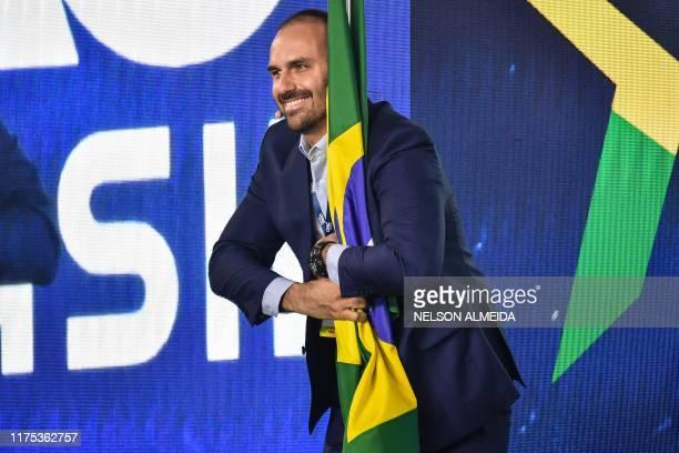 Brazilian Deputy Eduardo Bolsonaro son of Brazilian President Jair Bolsonaro holds a Brazilian national flag during the Conservative Political Action...