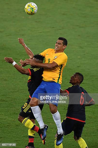 Brazilian Diego Souza contests the ball with Eder Alvarez and Fernando Uribe of Colombia during a friendly football match in benefit of Chapecoense...