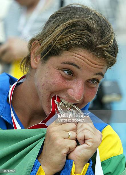 Brazilian diver Juliana Veloso bites her silver medal during the women's 10M platform podium ceremony 06 August 2003 during the 2003 Pan American...