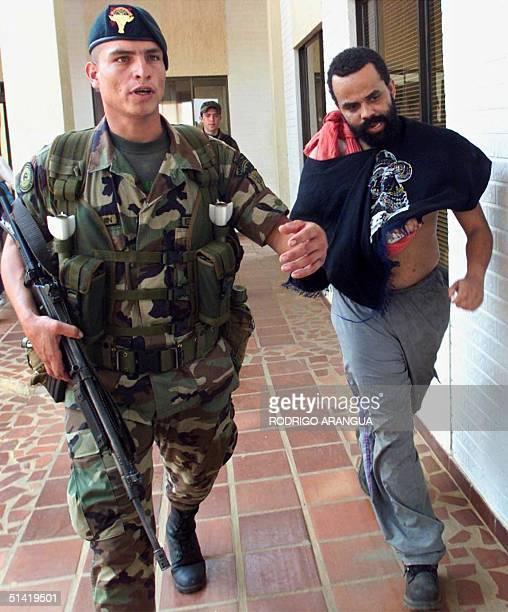 Brazilian drug kingpin Luiz Fernando da Costa is escorted by a soldier after being presented to the press 22 April 2001 at the Marandua de Bichada...