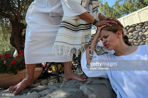 Brazilian Evangelist Christian is blessed by her priest who wears a Tallit or Jewish prayer shawl during a mass baptism ceremony in the Jordan River...