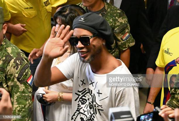 Brazilian exfootball star Ronaldinho Gaucho waves upon arriving at Silvio Pettirossi International Airport in Luque near Asuncion on March 4 2020...