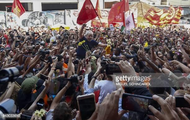 TOPSHOT Brazilian expresident Luiz Inacio Lula da Silva raises his fist after attending a Catholic Mass in memory of his late wife Marisa Leticia at...