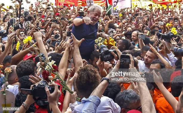 Brazilian expresident Luiz Inacio Lula da Silva waves to supporters after attending a Catholic Mass in memory of his late wife Marisa Leticia at the...