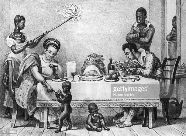 A Brazilian family at dinner on a coffee plantation circa 1820 The woman feeds scraps to a small black child whilst a female slave cools the air with...