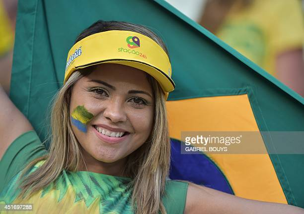 A Brazilian fan cheers before a quarterfinal football match between Brazil and Colombia at the Castelao Stadium in Fortaleza during the 2014 FIFA...