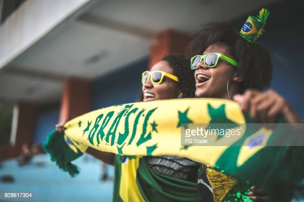 brazilian fan friends celebrating in a soccer game - world cup stock photos and pictures