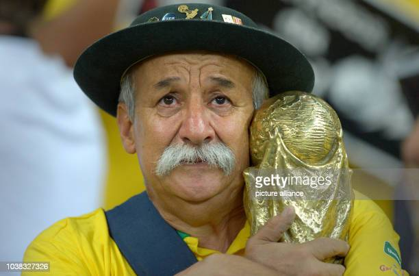Brazilian fan in tears holds a mock-up world cup trophy during the FIFA World Cup 2014 semi-final soccer match between Brazil and Germany at Estadio...