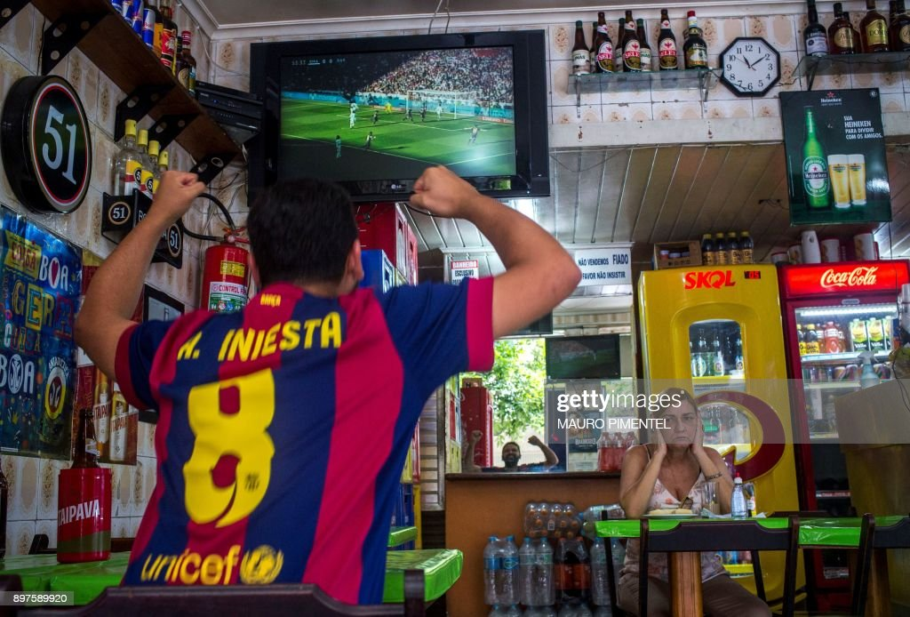 Brazilian fan of Spain's Barcelona celebrates the first goal against Spain's Real Madrid at a bar in Copacabana neighborhood in Rio de Janeiro, Brazil, on December 23, 2017. Barcelona took a huge step towards regaining the La Liga title as goals from Luis Suarez, Lionel Messi and Aleix Vidal beat bitter rivals Real Madrid 3-0 at the Santiago Bernabeu on Saturday to open up a 14-point lead over the European champions. /