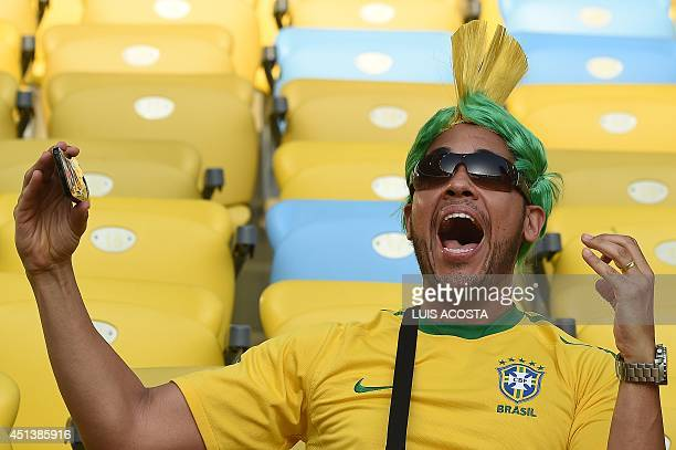 A Brazilian fan reacts as he watches on screen his team playing against Chile prior to the Round of 16 football match between Colombia and Uruguay at...