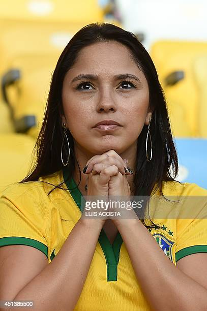 A Brazilian fan reacts as she watches on screen her team playing against Chile prior to the Round of 16 football match between Colombia and Uruguay...