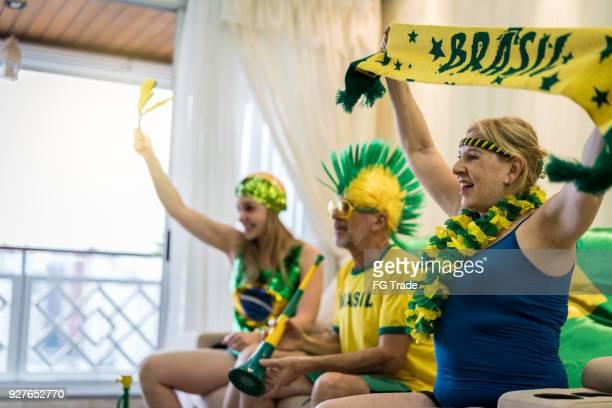 fã brasileiro assistindo jogo de futebol em casa - rodada da competição - fotografias e filmes do acervo