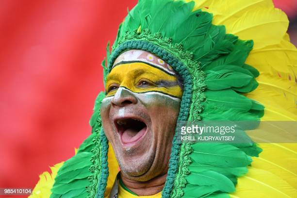 A Brazilian fan with his face painted in the colours of the national flag cheers his team as he poses outside the stadium before the Russia 2018...