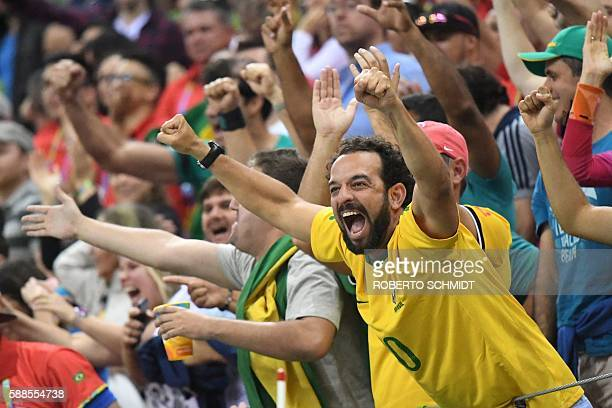 Brazilian fans cheer their team during the men's preliminaries Group B handball match Brazil vs Germany for the Rio 2016 Olympics Games at the Future...