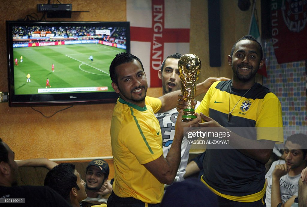 Brazilian fans hold a mock world cup trophy as they watch the 2010 World Cup football match between Brazil and North Korea at a coffee shop in Kuwait City of on June 15, 2010.