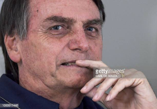 Brazilian far-right presidential candidate Jair Bolsonaro gestures as he talks to the press in Rio de Janeiro, Brazil on October 25, 2018. - The...